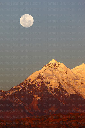 Full moon rising above north peak of Mt Illimani at sunset, Cordillera Real, Bolivia