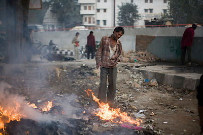India - Delhi - Homeless men gather round a fire at dawn