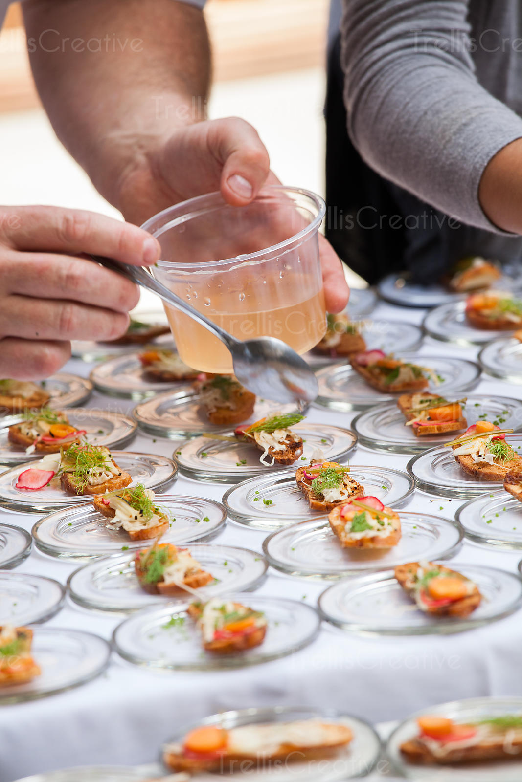 Chef garnishing the crostini bites with a vinegerette