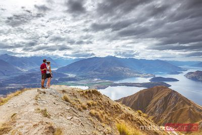 Tourist couple looking at beautiful landscape, New Zealand