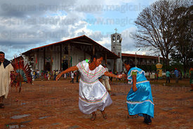 Women wearing traditional dress dancing in main square in front of Jesuit Mission church, San Ignacio de Moxos , Bolivia