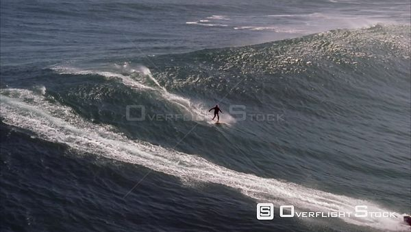 Aerial shot of a surfer riding a big wave with a dingy riding out front and alongside the surfer. Eastern Cape South Africa