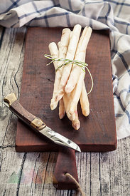 Bunch of white asparagus on wooden chopping board