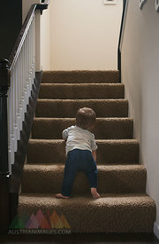 Little boy learning to go up a staircase