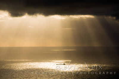 Single container ship sailing into patch of sea illuminated by sunbeams shining through storm clouds at sunset