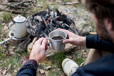 Man drinking coffee at campfire