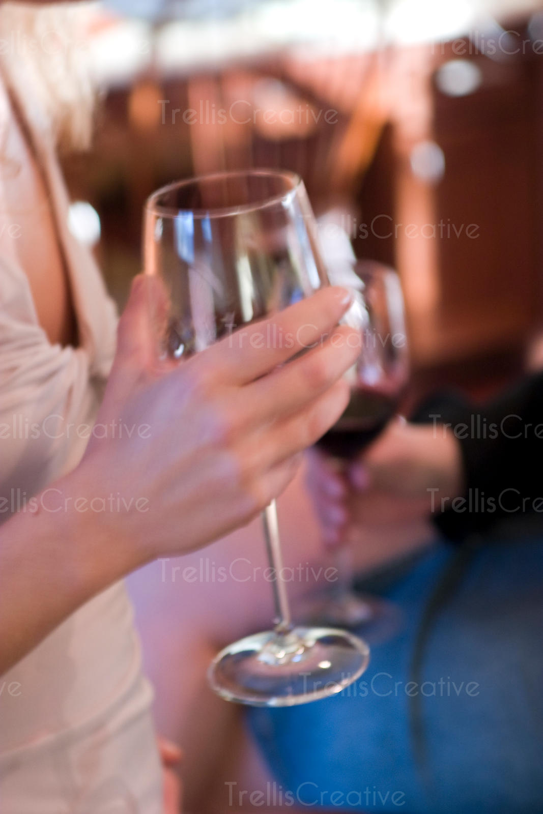 Close-up of a young woman's hand holding a glass of red wine