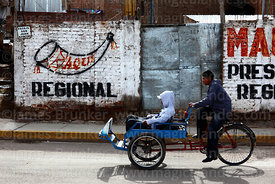 Tricycle taxi passing political party badge on wall, Puno, Peru