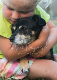 Young Girl Holding Small Senior Dog