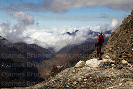 Hiker looking down Pajchiri Valley towards Estancia Cabaña Pampa on El Choro trail from pass, Cordillera Real, Bolivia