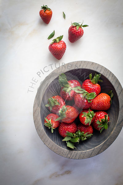 Strawberries in a grey wooden bowl on a marble table on top view