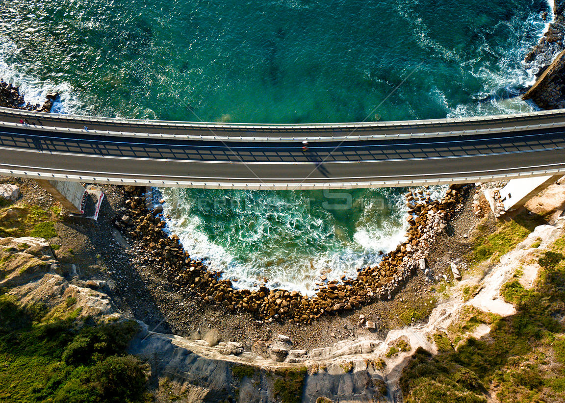 High above near the cliffs views down onto the Sea Cliff Bridge as a cyclist crosses leaving long shadows in the early mornin...