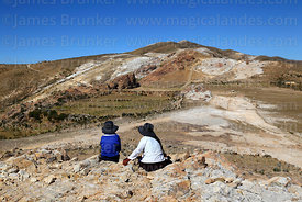 Local children sitting on rocky outcrop in Sanctuary area,  Sacred Rock / Titikala in background, Sun Island, Lake Titicaca, Bolivia