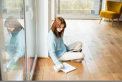 Young woman sitting on floor taking notes