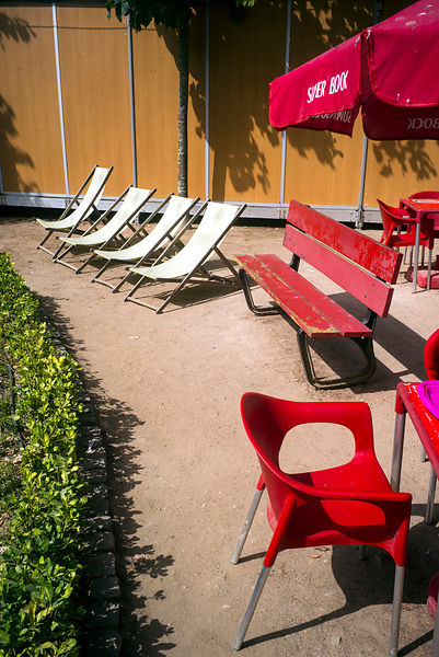 Deckchairs, red chairs and a bench at the cafe at the Jardim Botânico do Porto in Porto, Portugal