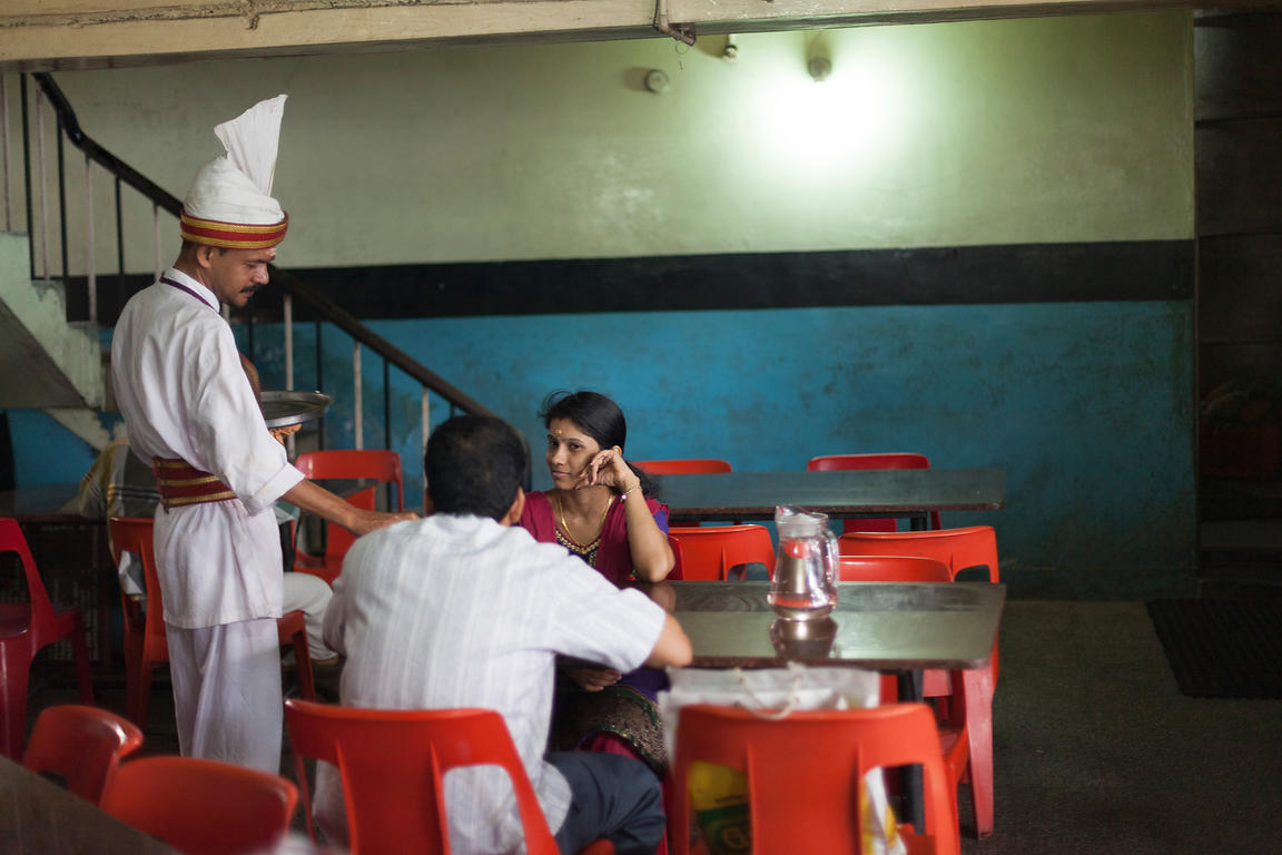 India - Thrissur - A waiter serves a couple at the Indian Coffee House