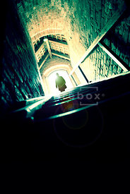 An atmospheric image of a mystery man standing at the top of some cellar steps, in an old building.