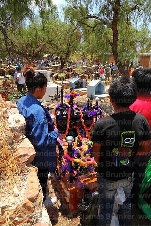 Children saying prayers for souls of the dead next to grave during Todos Santos festival, Sipe Sipe, Cochabamba Department, Bolivia