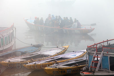 Misty winter morning boat rides for pilgrims on the Ganges River, Varanasi, India.
