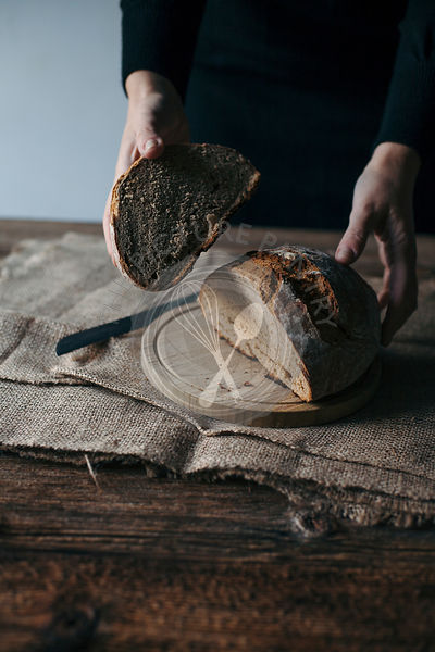 Woman slicing freshly baked rye bread on a rustic wooden table