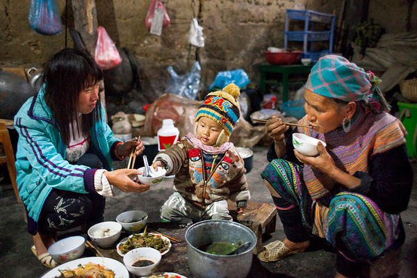 Trois génération mangeant ensemble dans leur cuisine à Bac Ha, Vietnam / Three-generation eating together in their kitchen in...