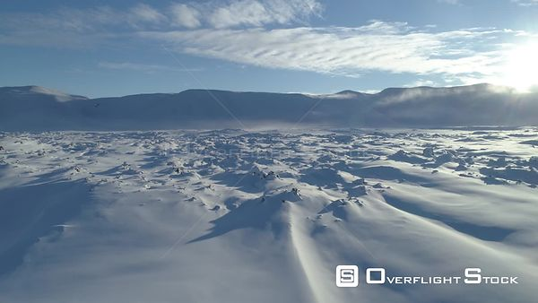 Low Over Snowy Lava Field Toward Mountains and Sun Iceland