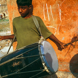 A boy practices his drum in the street