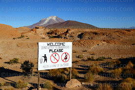 Sign telling tourists not to litter or use rock formations as a toilet, Cerro Ollagüe volcano in background, Nor Lípez Province, Bolivia