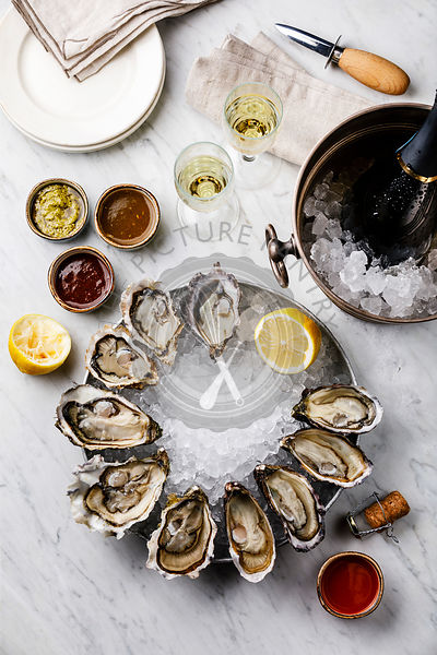 Open Oysters with lemon, sauce and Champagne in ice bucket on white marble background