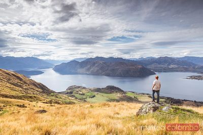 Man looking at landscape with lake and mountains, New Zealand