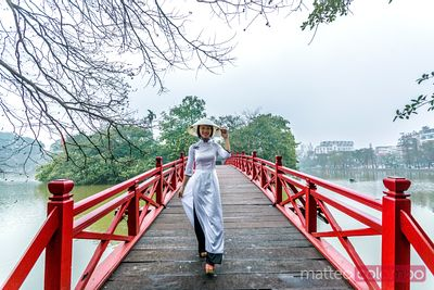 Young asian girl in Ao Dai dress on famous bridge, Hanoi, Vietnam