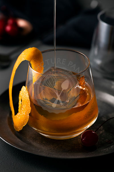 Old fashioned cocktail being poured into glass with large ice cube and orange swirl garnish.