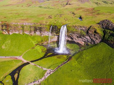 Aerial drone view of Seljalandsfoss waterfall with tourists, Iceland