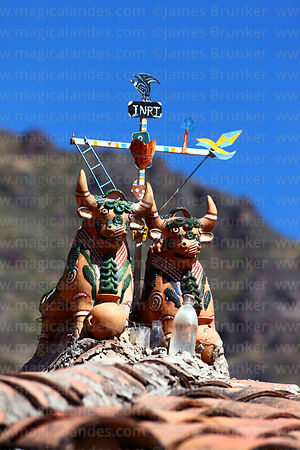 Ceramic bulls and cross with Andean condor and INRI abbreviation for protection on tiled roof of house, Pisac, Sacred Valley,...