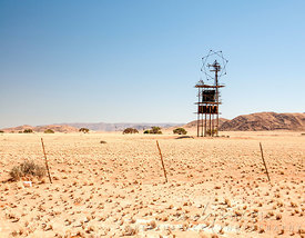 An old aerial antenna and elevated water tank in desert, rustic fence in foreground, sand dunes in distance