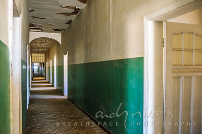 Sand covers the floor of a long passageway with many doors opening off it in an old abandoned Victorian-era building in a des...