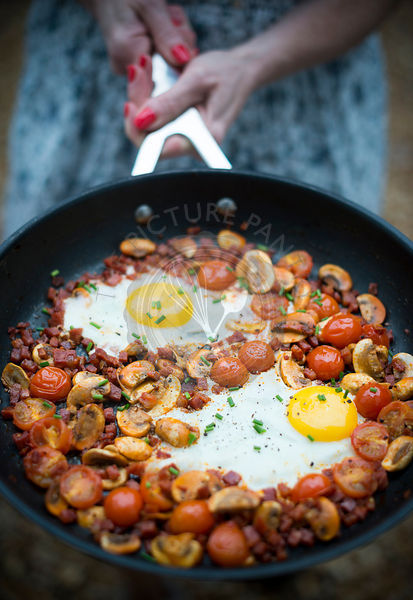Egg, mushroom, tomato and chorizo hash in a sausepan, held by a woman.