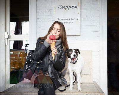 Germany, Dusseldorf, Young woman with dog eating icecream