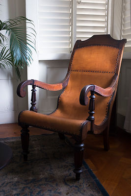 Ancien fauteuil à bascule en cuir et bois de la Devon House, construite en 1881, Kingston, Jamaïque / Old rocking chair made ...