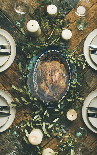 Flat-lay of whole roasted chicken in tray for Christmas eve celebration, plates, glasses and candles over rustic wooden backg...