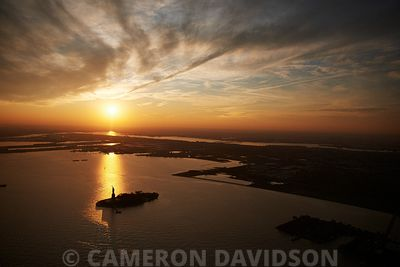 Aerial photograph of the Statue of Liberty in New York Harbor at sunset..