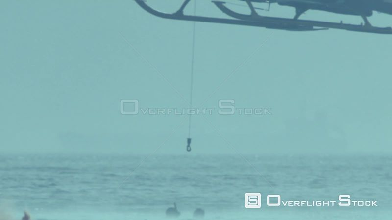 Aerial slow motion shot of a rescue helicopter lowering a rope down to two men in the sea Cape Town Western Cape South Africa
