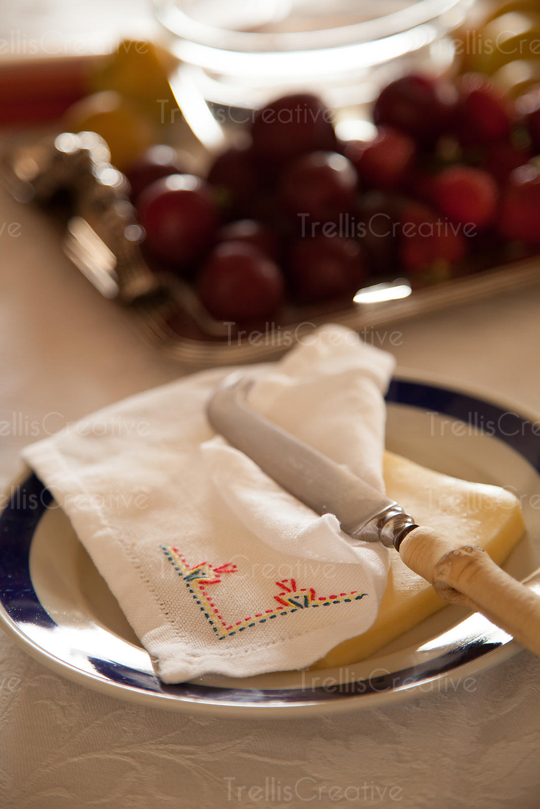 Morning light shines onto a table with cheese slices and fruit on it
