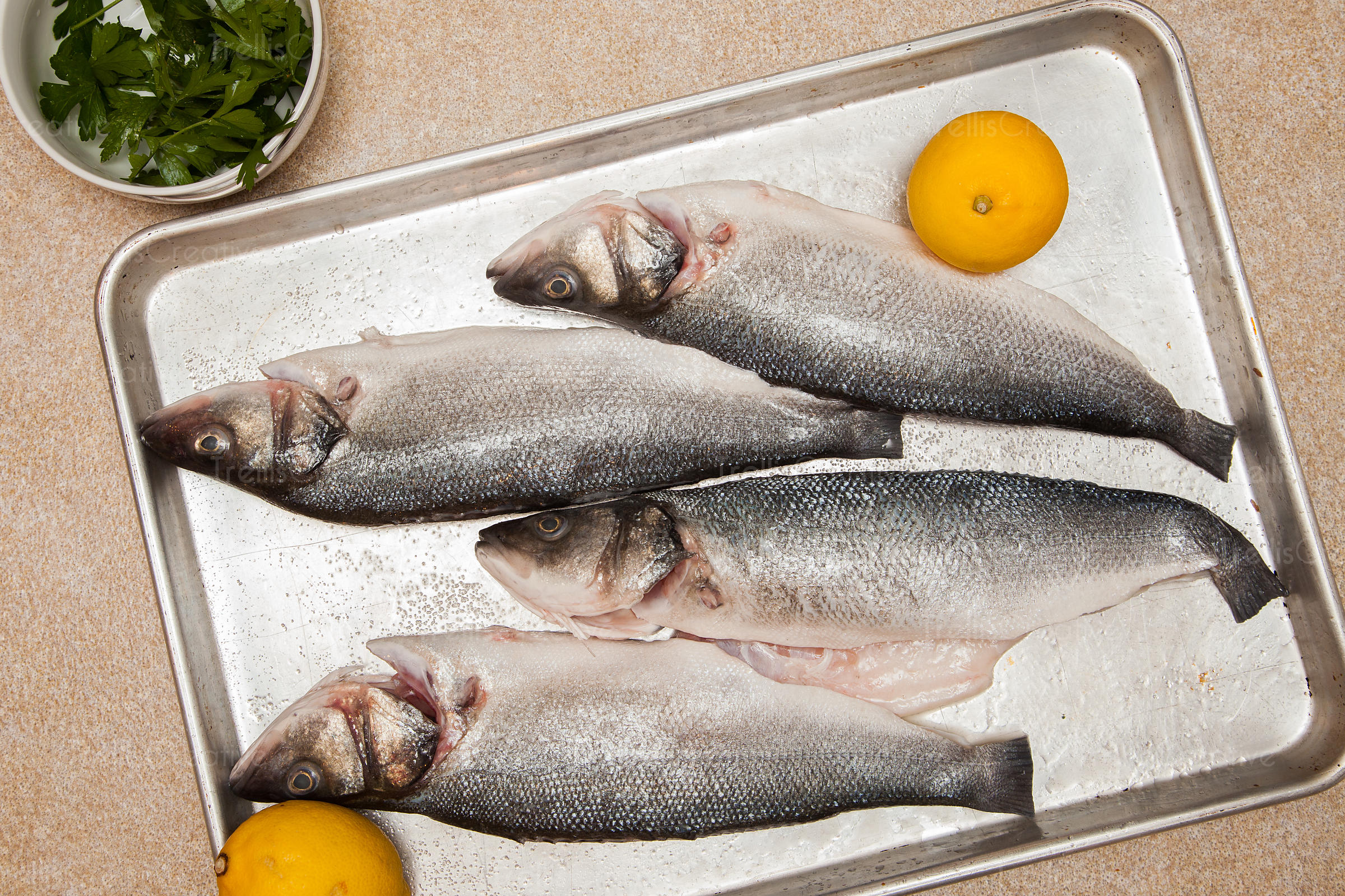 Whole fresh raw fish with lemon on tray