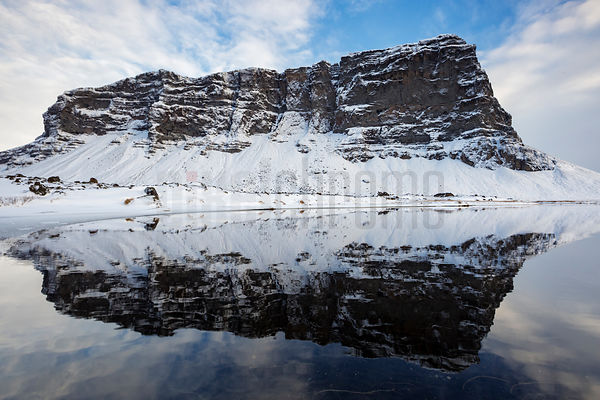 Reflection of Mt Lomagnupur in an Ice Melt Pond