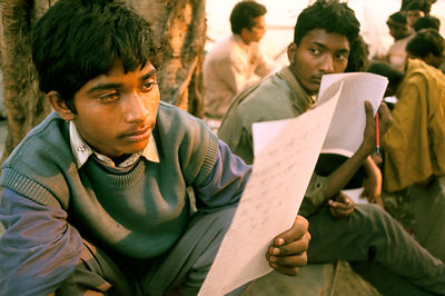 India - Delhi - Child labourer reading his homework after class