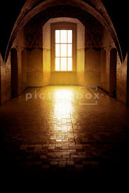 An atmospheric image of the sun coming through a window, in an old, empty room.