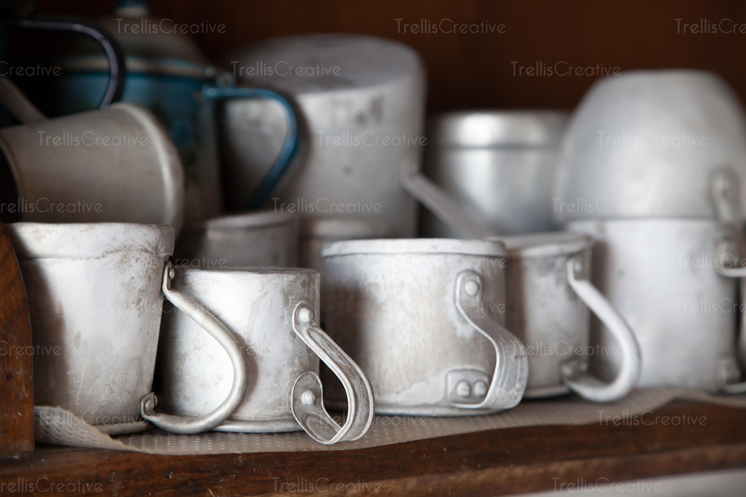 Old aluminum mugs on a wood shelf in a country ranch house
