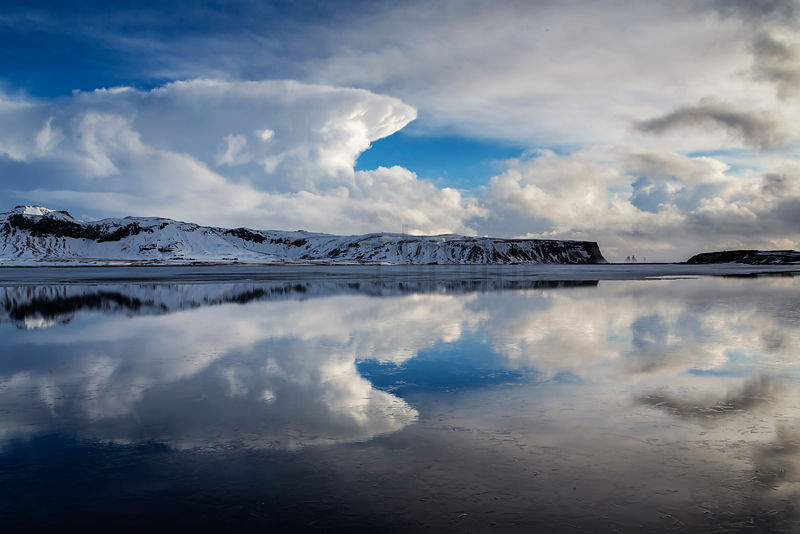 View of Reynisfjara Reflected in a Melt Pond