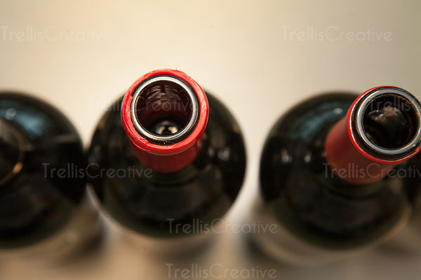 Top view of three bordeaux style bottles with foils cut.